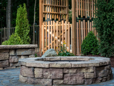 Rosetta Stone Fire Pit and Seating wall in front of custom cedar arbor located in Metamora, MI.