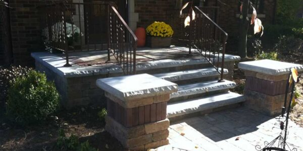 Unilock brussels front porch with pillars accented with copthorne and ledgestone coping and LED landscape Lighting with restored iron railing locatedin Genesee County, MI