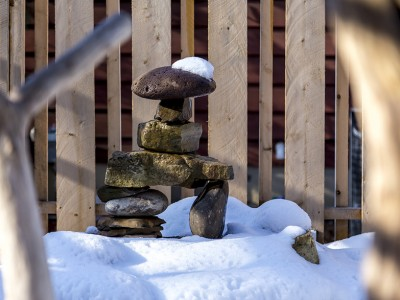 Stacked stone arrangement to look like a man in winter with snow covered ground and a snow cap on the top of the figures head located in Flint, MI