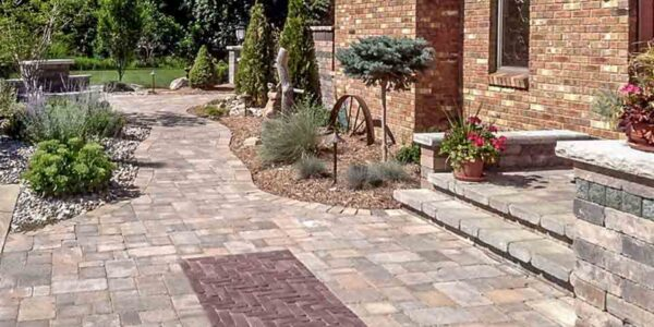 Unilock Brussels paver walkway with steps and porch and copthorne paver rug and water feature in background and unigranite pillar accents located in flint township, MI