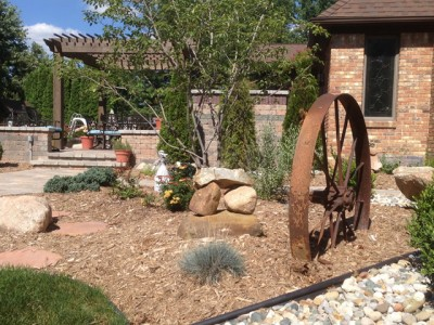 stacked stone arrangement with iron wagon wheel and pergola located in Flint township, MI