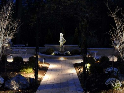 Moonlight garden lit by kitchler landscape lighting system with pathlights and integral lights mounted in retaining walls and pillars and statue lit too