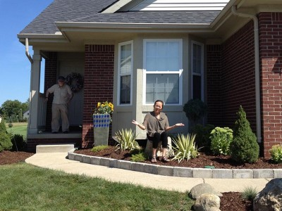 Front of condo located in Grand Blanc, MI landscape shown with happy clients