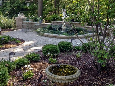 moonlight garden shown without all white floowers and with unilock brussels patio and seat wall with landscape lighting and statue in Flint, MI