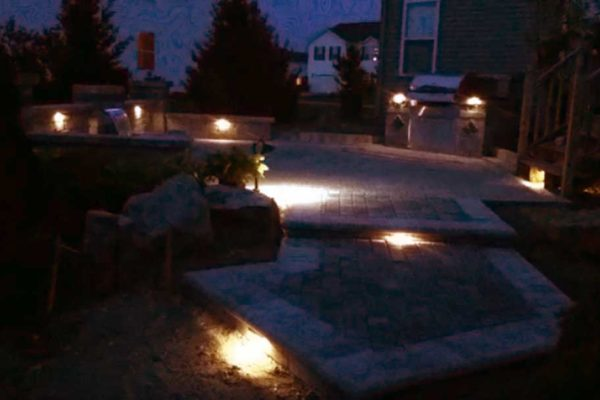 Outdoor living space shown at night lit by landscape lights in Davison, MI