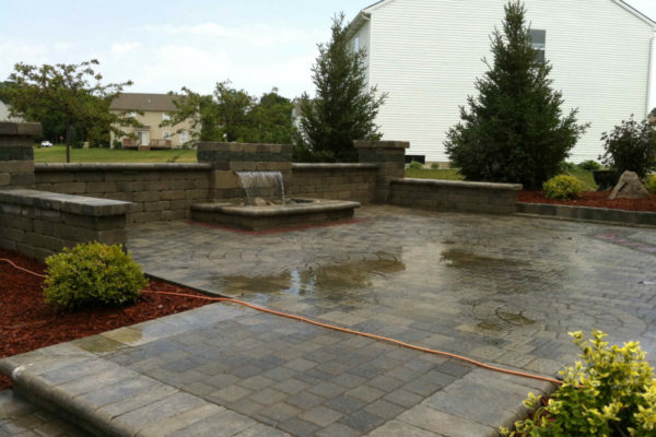 Formal Falls water feature with unilock seating wall, pillars and olde greenwich patio located in Davison, MI