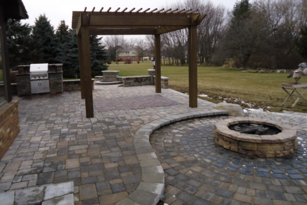 OUtdoor LIving space during construction. Custom Cedar pergola, Rosetta round fire pit, gas built-in grill and water featurein early winter located in Flint township, MI