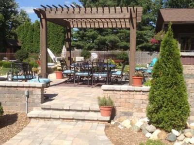 Custon cedar pergola, unilock patio and seating walls with pillar and steps. LED landscape lighting located in Flint Township, MI