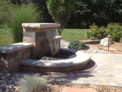 Formal fall water fall with unilock wall and pavers and real limestone cap outdoor living area located in Flint Township, MI