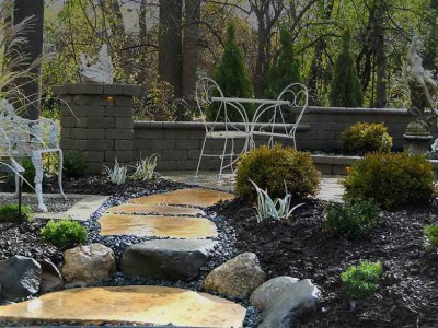 moonlight garden shown after rain with deerskin large flagstone walk to unilock brussels patio and seat wall with landscape lighting and statue in Flint, MI