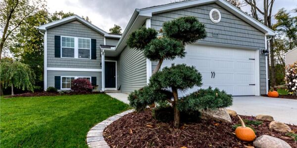 poodle pine in foreground of a wide angle shot of front of landscaped home in Howell, MI