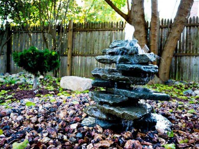 Stacked blue stone bubbling water feature in autumn located in Grand Blanc, MI