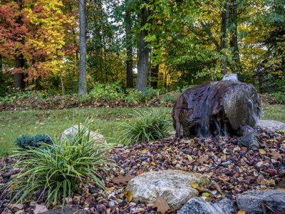 Hand drilled bubbling boulder shown in autumn with ice dance sedge and decorative stone in Grand Blanc, MI