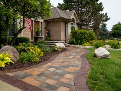 Unilock Brussels Desert Sand with Copthorne Soldier Course accents front walkway with a Ledgestone Coping Steps and Porch home located in Grand Blanc, MI.