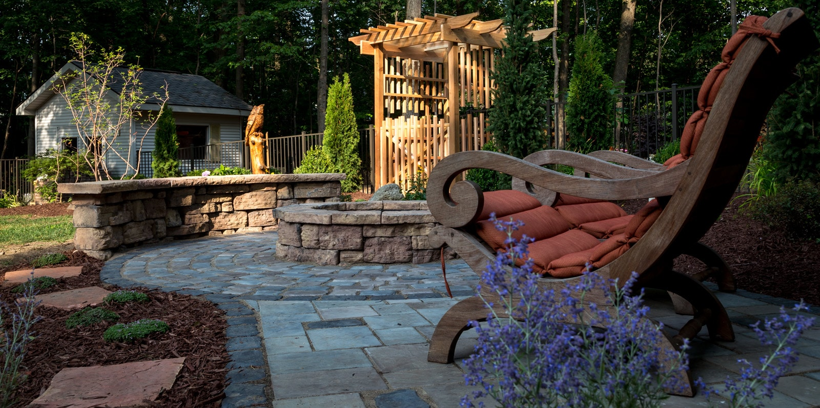 Outdoor Living Space located in Metamora, MI with a cedar Arbor, Rosaetta fire pit and seating wall and Unilock Richcliff Paver Patio.